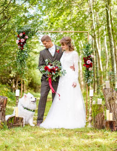 Bride and Groom photo in front of a copper floral arch with their dog in a forest