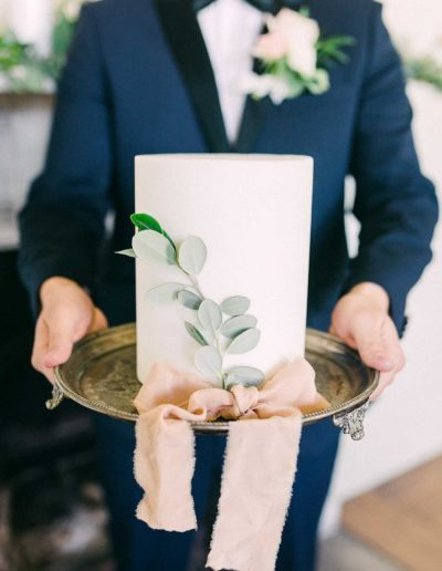 Fine art Wedding cake and groom with flowers by Flourish and Grace