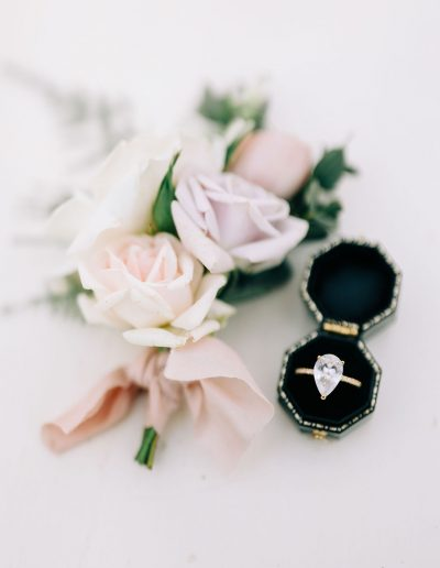 Wedding ring in box and buttonhole flatlay with flowers by flourish and grace