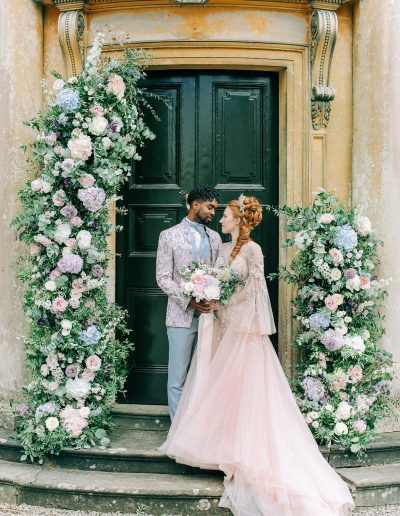 Bridgerton inspired Bride and groom with wedding floral arch flowers by Flourish and Grace