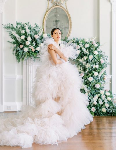 Bride surrounded by wedding fireplace flowers and mantlepiece flowers by Flourish and Grace