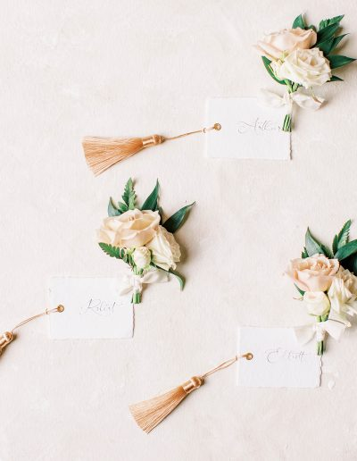 Wedding stationery and buttonholes boutonnieres flat lay with flowers by Flourish and Grace
