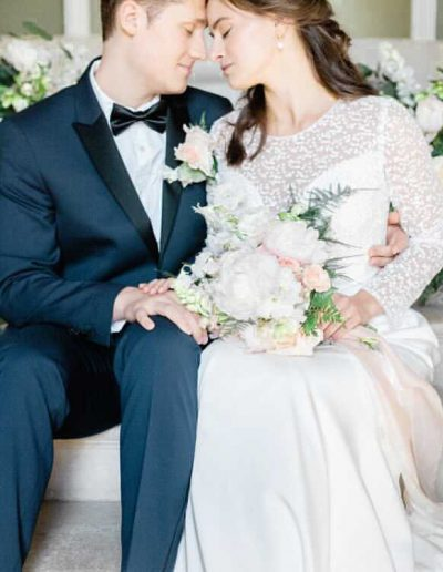 Bride and groom with wedding bouquet surrounded by flowers by Flourish and Grace