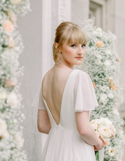 Brides in TH&H wedding dress with bouquet and flower arch by Flourish and Grace, Bristol Wedding Florist