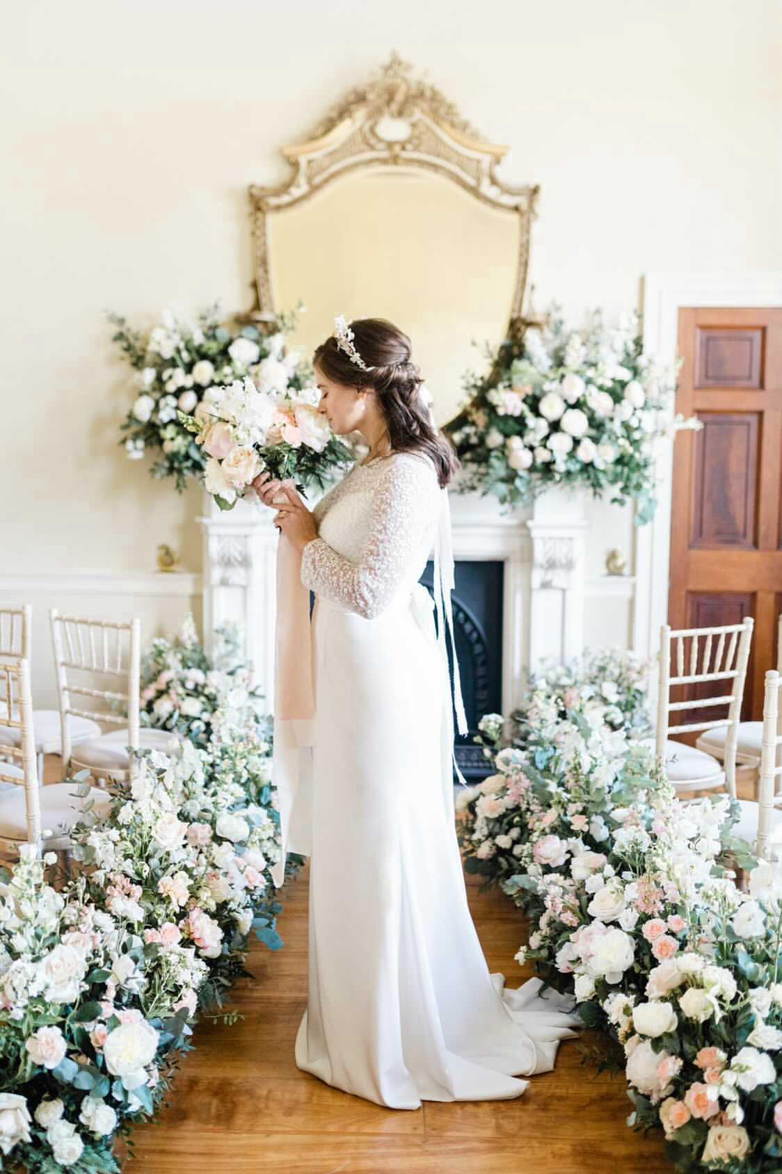 Bride with wedding bouquet surrounded by aisle flowers and mantlepiece flowers by Flourish and Grace