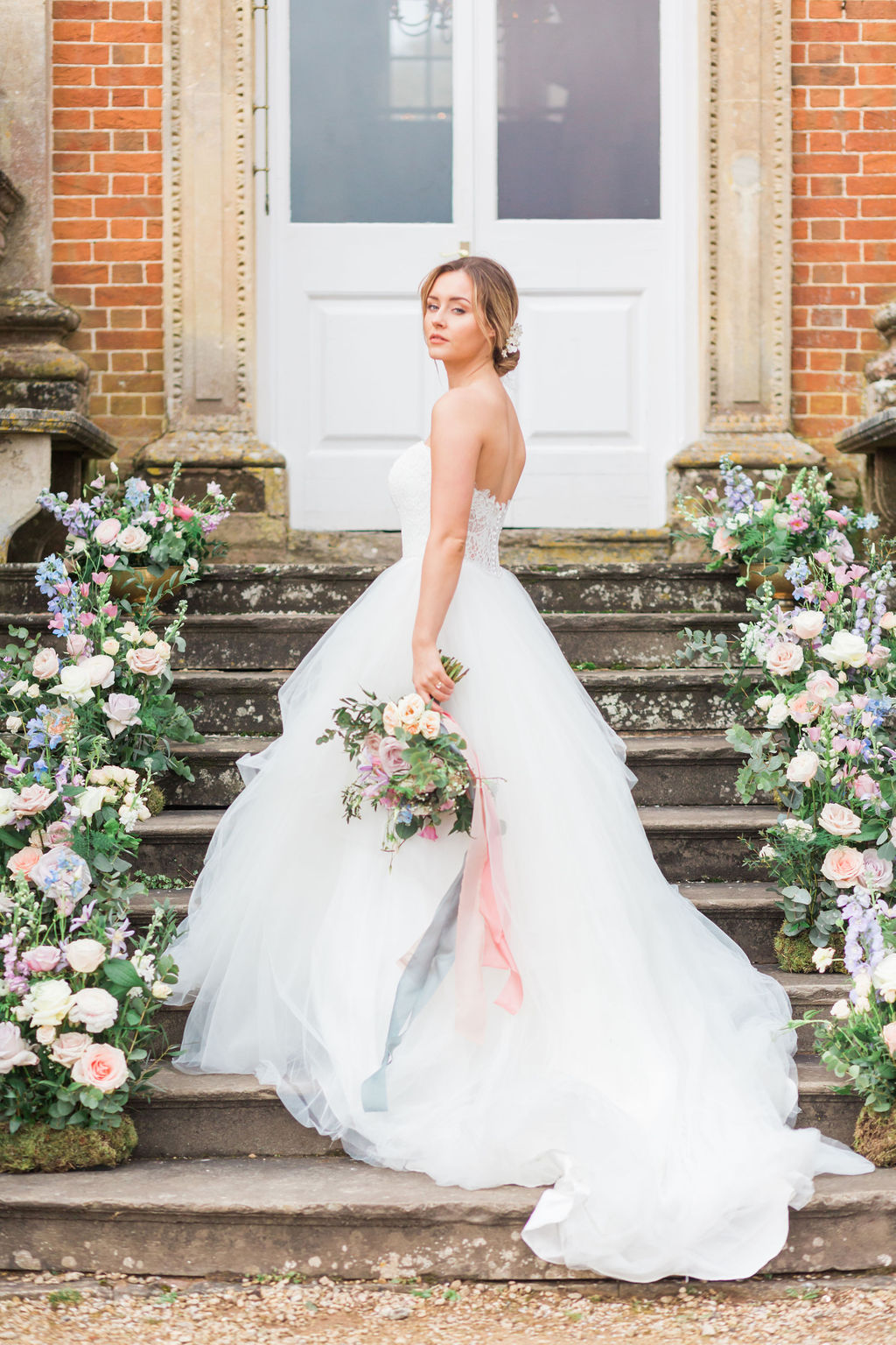 Staircase with flowers and fine art bride with wedding bouquet by Bristol florist Flourish and Grace