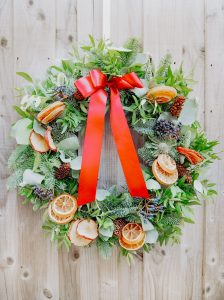 Traditional Christmas wreath with festive decorations fruit slices pinecones and ribbon for delivery Bristol postage across the uk