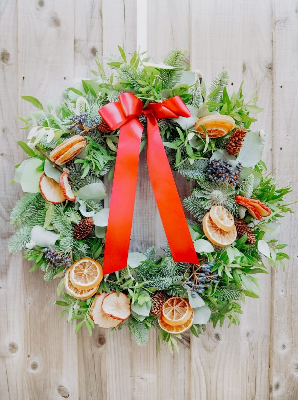 Traditional Christmas wreath with festive decorations fruit slices pinecones, berries and ribbon for delivery Bristol postage across the uk