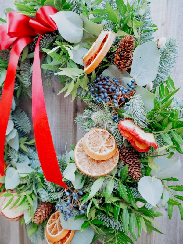 Traditional Christmas wreath with festive decorations fruit slices, pussy willow, pinecones, berries and ribbon for delivery Bristol postage across the uk