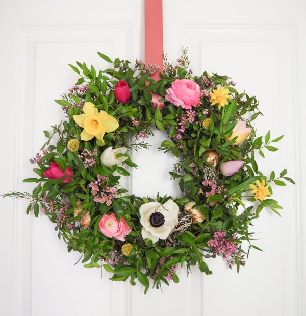 Flourish and Grace Spring wreath kit hung on the door with mossed wreath and flowers