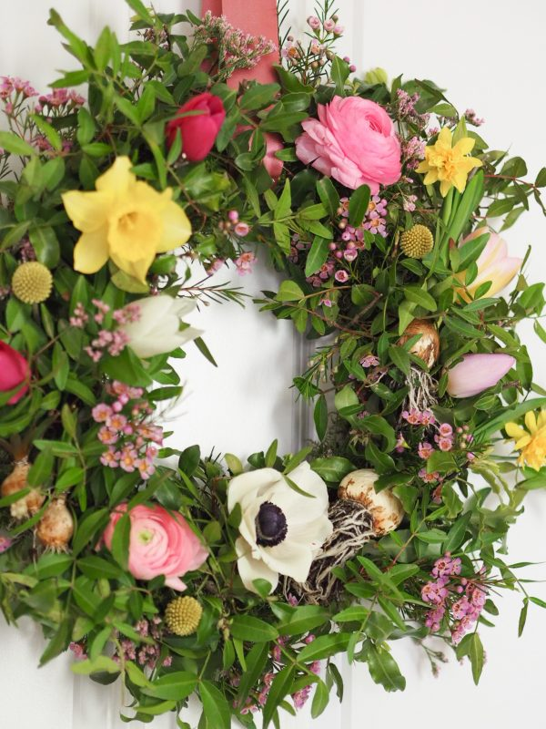 Flourish and Grace Spring wreath kit hung on the door with mossed wreath and flowers anemones daffodils tulips and ranunculus